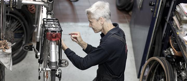 Trabajadora de edad madura en taller de bicicletas