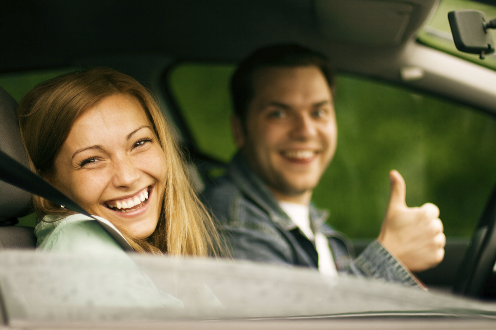 happy-couple-driving-thumbs-up